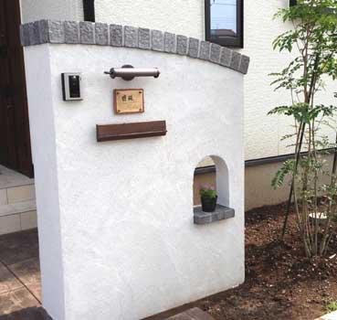 レトロな表札灯、銅製の表札、木目調のポストの白い塗り壁