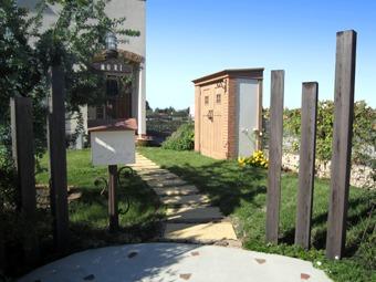 門まわりとアプローチ。途中にあるカンナ物置がアクセントになっている