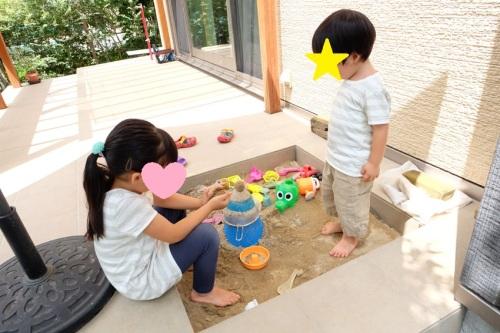 テラスの中に作った砂場で遊ぶお子さんの写真