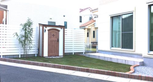 隣地境界に白い目隠しフェンスとカンナキュートを設置したお庭の写真