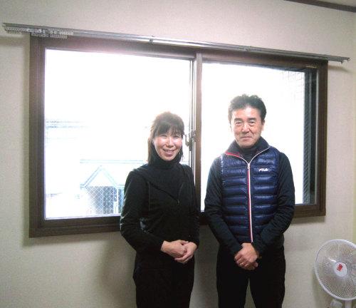 内窓プラマードUを設置した後の 勉強部屋の窓(道路側)の前に笑顔で立つお客様の写真
