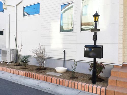 ポストと立水栓がある花壇施工後の写真