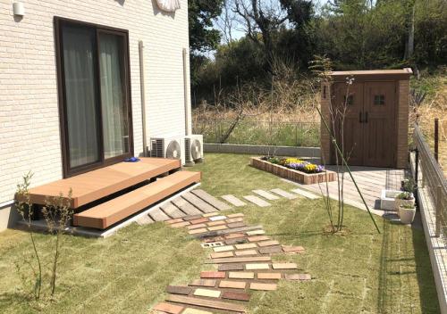 ウッドデッキ、テラス、カンナ物置などのある施工後のお庭の写真