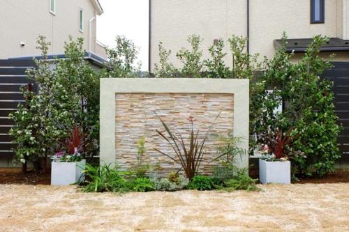 グリーンの植栽の前にアクセントウォールが設置された写真