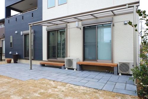 平板を敷いたテラスとテラス屋根を設置した庭の写真