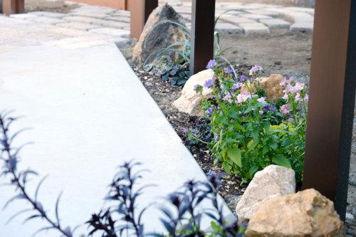 フェンスの下に植えた花とコッツウォルドストーンの写真