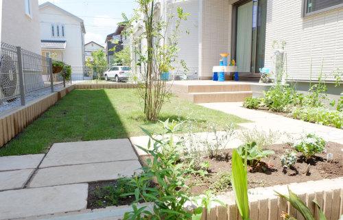 芝生、シマトネリコ、花壇の花々が入った植栽後の写真
