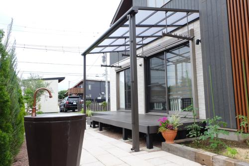 デッキ上にLIXILのテラス屋根【スピーネ】を設置したお庭の写真