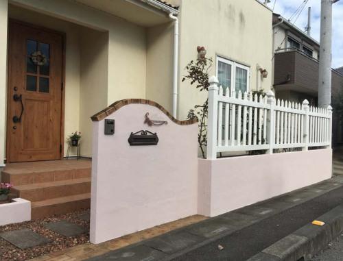 【淡いピンクに塗りなおした門壁と塀の様子】