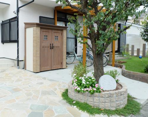 乱形の石張りと丸い花壇、無垢材のサイクルポートとカンナがある庭