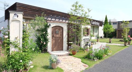 芝生、バラ、樹木、草花であふれたお店の写真