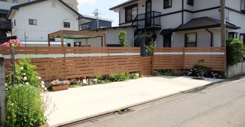 フェンスの足元や奥に植物が見えて華やかな印象の写真