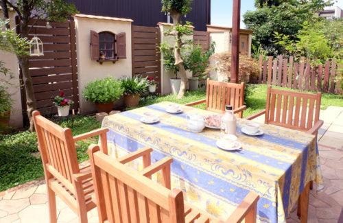 完成したお庭の写真。手前には天然木のファニチャーとその奥にはディゴンドラの緑の床と目隠しフェンスと南欧風の壁が見えるお庭