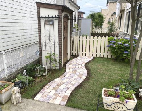 緑の芝生の中にできたレンガ調のカワイイ小道が、庭の奥にある物置へとつづきます