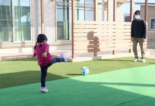 人工芝のお庭でサッカーをするお子さん